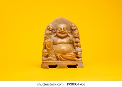 Small soapstone smiling buddha statue. Studio souvenir still life against a seamless yellow background.