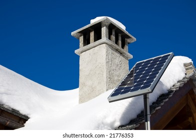 A small solar panel installed on a mountain house roof