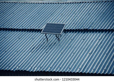 A small solar panel unit on a tin shed roof isolated unique photo