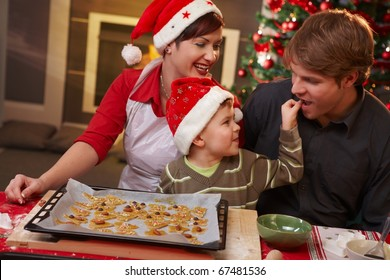 Small son helping dad tasting christmas cake at table, mother watching, laughing.