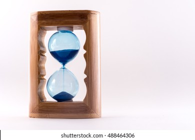 Small souvenir wooden hourglass with blue sand