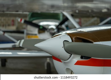 Small Sport Aircraft parked in hangar, close up. detail view of front, nose, cowling and propeller, piston aircraft
