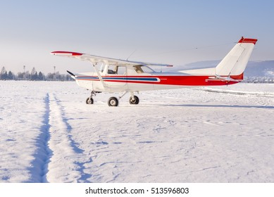Small sport airplane with white fuselage and red and blue stripes on the apron. The airport is covered in fresh snow on a sunny day.