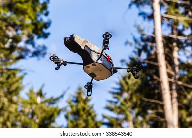a small spy quad copter scout drone flying through the trees in a forest