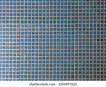 small square ceramic tiles in different shades of blue with white grouting background