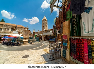 Small square with fountain among gift shops as belfry on background in Muristan - famous historic complex of streets in Christian Quarter of Old City of Jerusalem, Israel.