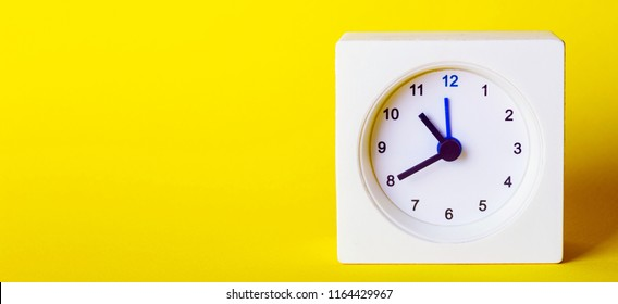 small square white clock on ayellow  background