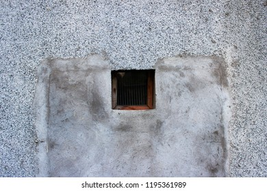 a small square window with a wooden frame leading to the basement, covered with fine grating and glass