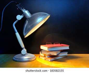 Small stack of books with glasses and vintage lamp in front of black wall
