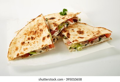 Small stack of cooked wheat tortilla quesadillas parts stuffed with onion, tomato and herbs in wax paper on white background