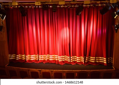 A small stage lit up with spotlights closed by a red curtain.