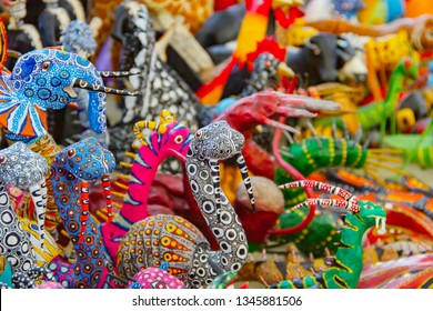 Small stand full of traditional Mexican alebrijes painted in many colors and shapes made by artisans from Michoacan