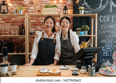 小規模な起業企業のオーナーコンセプト。2人の成功した若いバリスターがカフェのバーカウンターに立つ。喫茶店のカメラに自信を持ってほほ笑むエプロンの幸せなコーヒー店の仲居。