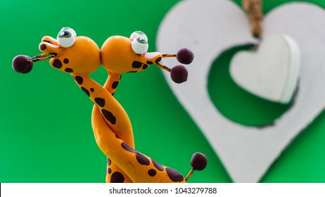 A small statue in the shape of yellow giraffes. They hug each other by the neck and finally give a kiss, on a green background and a white heart.