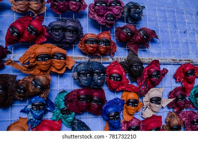small statues of masked faces hanged on a blue wall - touristic souvenir from Aswan - Egypt