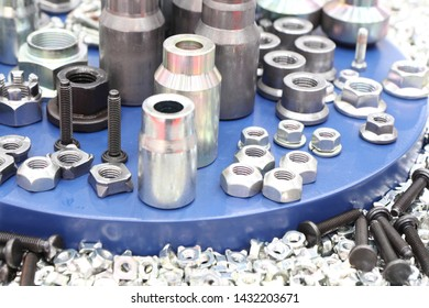 small steel bolts and nuts made by manufacturing process ; tapping process ; industrial background