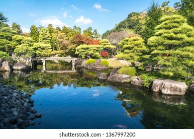 Small stone bridge over the pond, full of koi fish, at Koko-en Garden in autumn, with the rooftop of Himeji Castle just peeking over the tree line, in Japan.