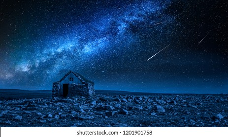 Small stone cottage and milky way with falling stars, Iceland