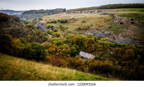 Small stone cottages in a valley, taken from above surrounded by autumnal trees, fields and hills. Taken near Buxton in Derbyshire Peak District, UK
