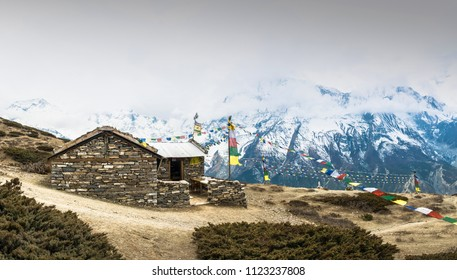 A small stone house on the background of snowy mountains on the trail to the Ice lake, Nepal.