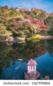 A small stone lantern in the lake at Koko-en Garden in autumn, with Himeji Castle rooftop just showing over the tree line in Japan.