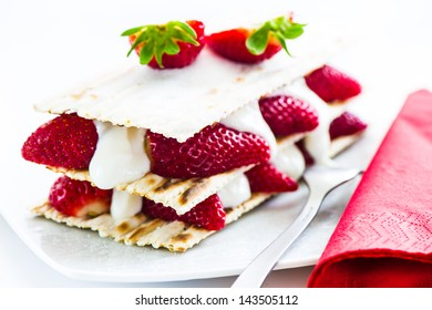 small strawberry cake with cream on white background