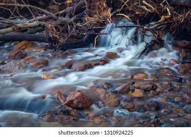 Small stream breaks through the wooden dam.