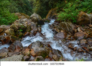 A small stream with rocks on Annapurna trekking trail at summer day in Nepal.