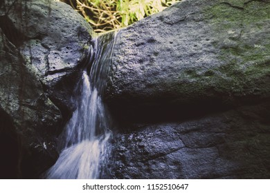 A Small stream of water flowing down between two rocks