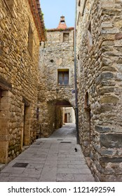 Small street in Besalu with medieval gate, Girona province, Catalonia, Spain
