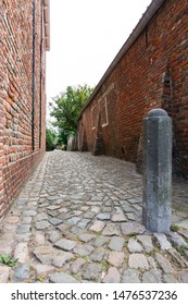 small street with cobblestones, brick wall and bollard. Veere, The Netherlands