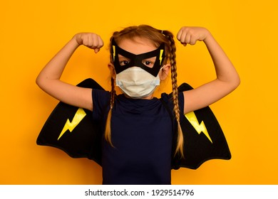 A small strong pretty girl in a superhero carnival costume in a black mask and wings and in a medical mask clenches her hands into fists to show her strength. The child fights diseases and infections