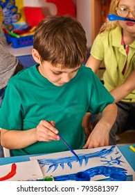 Small student boy painting in art school class. Child drawing by paints on table. Boy in a children's club. Craft drawing education develops creative abilities of children. Girl is pranking prank.