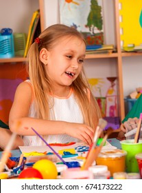 Small student painting in art school class. Child girl drawing by paints on table. Shelves for creativity background in kindergarten. Drawing education develops creative abilities of children.