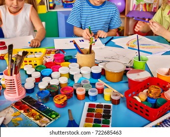 Small students girl and boy painting in art school class. Children drawing by paints on table. Male kid shows his drawing in kindergarten. Preparing for a children's art exhibition.