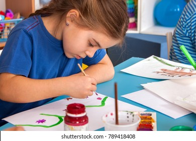 Small students painting in art school class. Child drawing by paints on table. Kid on balloons background. Psychological child test in kindergarten.