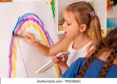 Small students painting in art school class. Child drawing by paints on table. Kid on balloons background. Top view of girl in kindergarten. newcomer in a children's team.