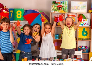 Small students with teacher finger painting in art school class. Teacher cheers children in kindergarten. Mom and kids at home. Craft drawing education develops creative abilities of children.