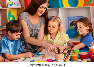 Small students with teacher finger painting in art school class. Break school in painting class. Mom and kids at home. Modern methods of teaching children through game.