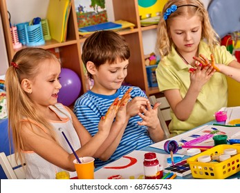 Small students with teacher finger painting in art school class. They get their hands dirty in the paint. Craft drawing education develops creative abilities of children.