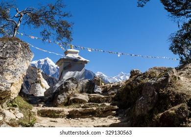 Small stupa with Tibetan flags on the way to Everest base camp. Mount Everest and Lhotse are seen at the background.