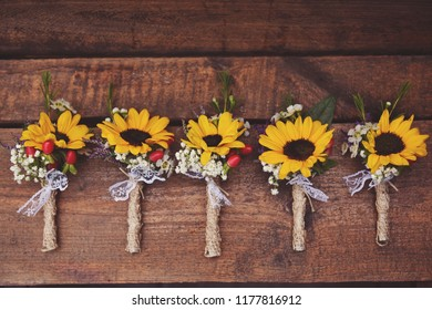 Small sunflower boutonnieres on a wooden table