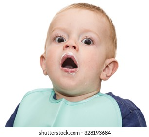 the small surprised fair-haired child with brown eyes in a green bib with an open mouth and the soiled lips