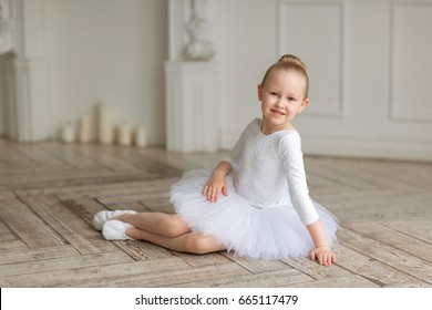 A small sweet ballerina in a white tutu and a body sitting on the birchwood floor in a light studio. Studio. Children and ballet
