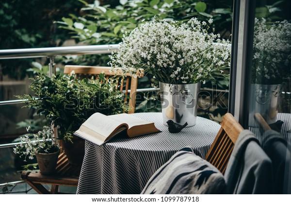 Маленький стол, книга и цветы на красивой террасе или балконе