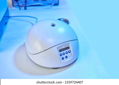 Small table centrifuge in biochemical laboratory. Institute of Organic and Biochemistry. Closeup table medical centrifuge. Researcher saperates supernatant and pellets by table top mini centrifuge.
