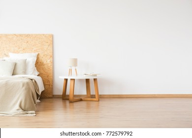 Small table with a lamp and books standing by the bed in white bedroom interior
