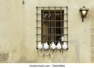 Small table lamps hanging on iron window bars. Old building exterior with stone surface.