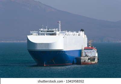 A small tanker on the roadstead bunkers a large ro-ro ship.