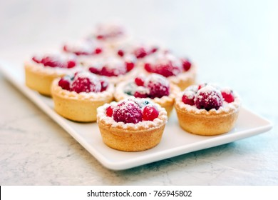 Small tarts with berries on white plate.